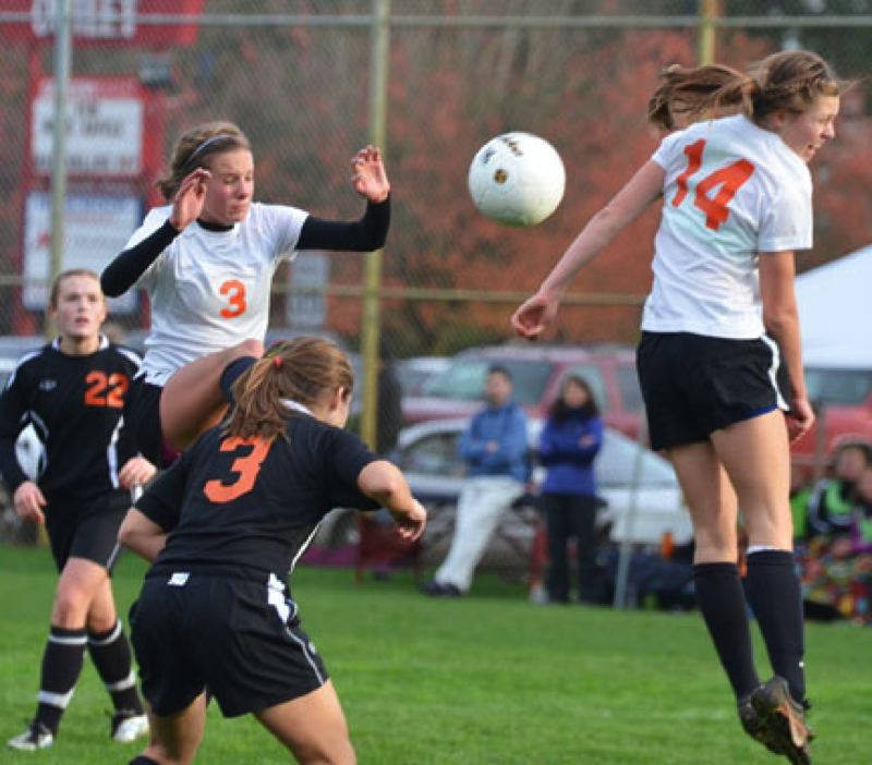 by: JOHN BREWINGTON - Scappoose's Eleanor Jones (14) and Natalie Muth (3) try to score off a corner kick during last week's game with Gladstone. Ariel Viera (17 below) drives the ball down the pitch. It was Viera's last soccer match for the high school. She scored 116 goals in her career.