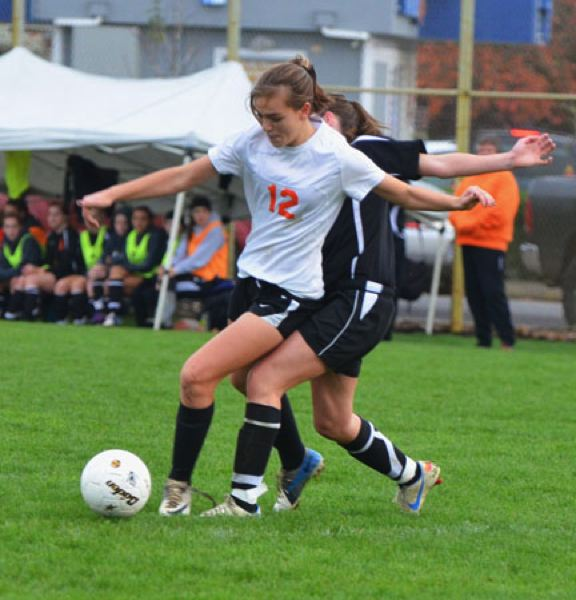 by: JOHN BREWINGTON - Scappoose's Natalie Muth was marked pretty closely by a Gladstone player during last Tuesday's semifinal match. The Lady Indians held Gladstone scoreless in the first half, but would lose the match.