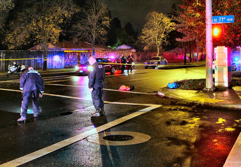 by: DAVID F. ASHTON - Officers look for evidence, after a man was hit in, and thrown out of, a Powell Boulevard crosswalk at S.E. 71st by a SUV which then fled the scene. The pedestrian, David Charles Eklund, died from his injuries.