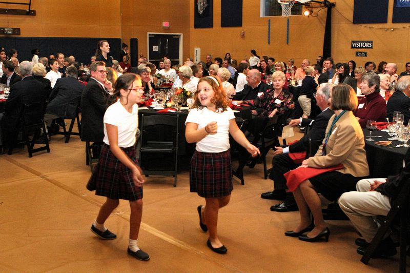 by: DAVID F. ASHTON - All over the room, students sing and dance to the delight of parents and supporters at the St. Agatha fundraising dinner.