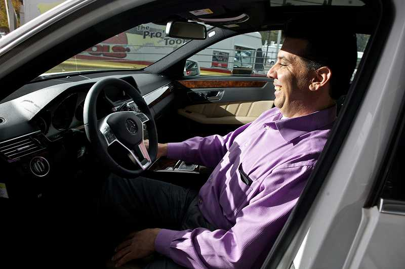by: JAIME VALDEZ - Terry Tallerino, general manager of the brand-new Mercedes-Benz of Beaverton on Southwest Canyon Road, demonstrates the features of a new vehicle in the dealership's newly constructed showroom.