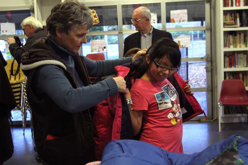 by: TIMES PHOTO: JONATHAN HOUSE - Rotary vounteer Marilyn Henderson helps Perla Ortiz try on a jacket at Greenbrug Oaks apartments.