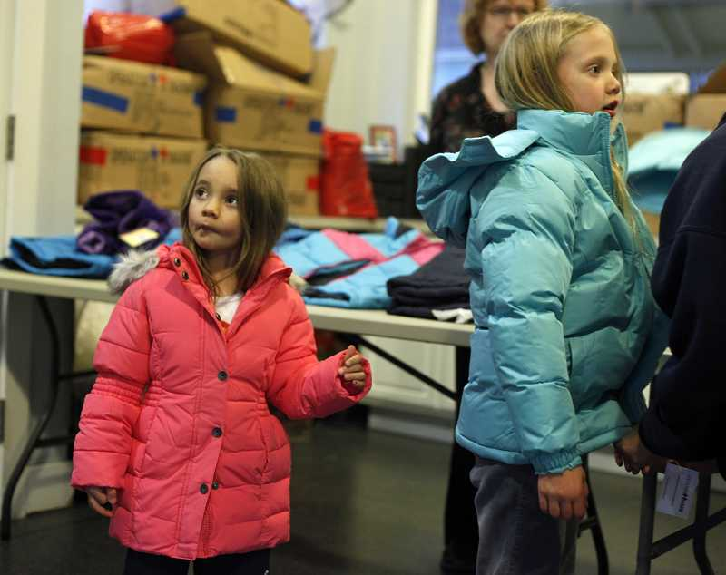 by: TIMES PHOTO: JONATHAN HOUSE - CPAH volunteers help children and parents with finding the right coat during their annual coat drive at Greenburg Oaks apartments.