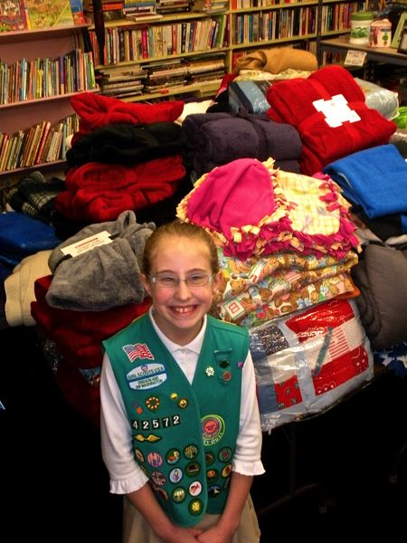 by: POST PHOTO: JIM HART - POST PHOTO: JIM HART Kalani shows her pride of accomplishment, standing in front of a pile, taller than her, of 103 blankets she collected for homeless people in the Sandy area. They will be distributed through the Sandy Community Action Center.
