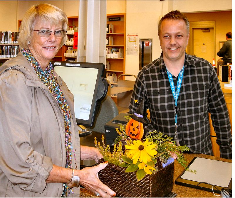 by: MERRY MACKINNON - Woodstock Library staffperson Marty Leisure admires the flower arrangements created and donated by Nancy Carr (left), on behalf of her garden club. Carr lives not far from the library, on S.E. 52nd.