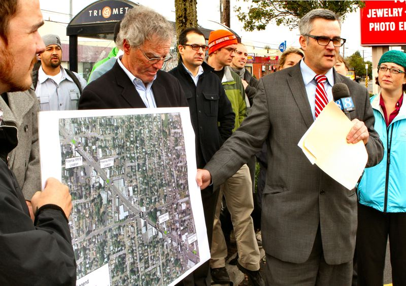 by: DAVID F. ASHTON - Portland Mayor Sam Adams points to locations where Rapid-Flashing Beacons will be installed to help protect pedestrians crossing S.E. Foster Road.