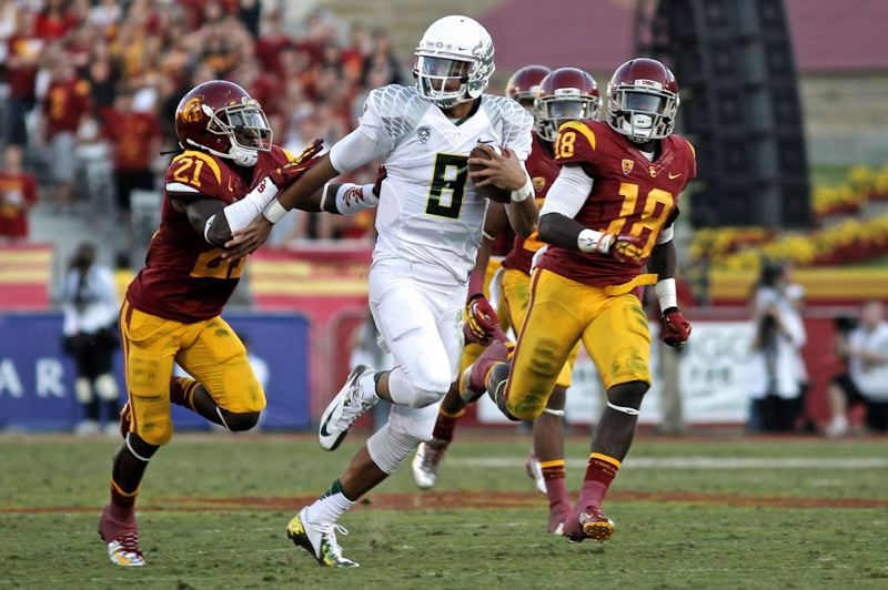 by: TRIBUNE PHOTO: JAIME VALDEZ - Oregon Ducks quarterback Marcus Mariota sprints through the USC defense.
