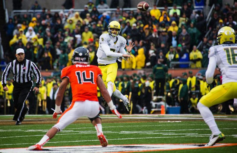 by: TRIBUNE PHOTO: CHRISTOPHER ONSTOTT - UO quarterback Marcus Mariota whips a jump pass up the field against Oregon State.