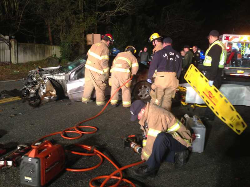 by: SUBMITTED - Lake Oswego firefighters work to extricate a man pinned inside of his wrecked car on Highway 43 early Monday.