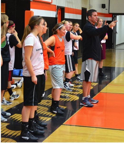 by: JOHN BREWINGTON - Scappoose Coach Kevin Buse directs traffic for a drill during practice last week at Scappoose High. The Tribe hosts St. Helens Thursday.