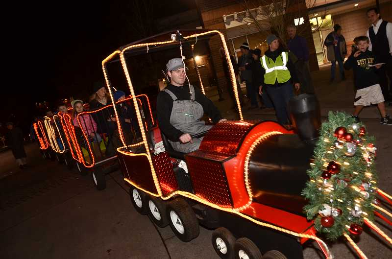 by: VERN UYETAKE - Michael Davenport of Clowns Unlimited drove the Christmas train last year through the Willamette neighborhood.