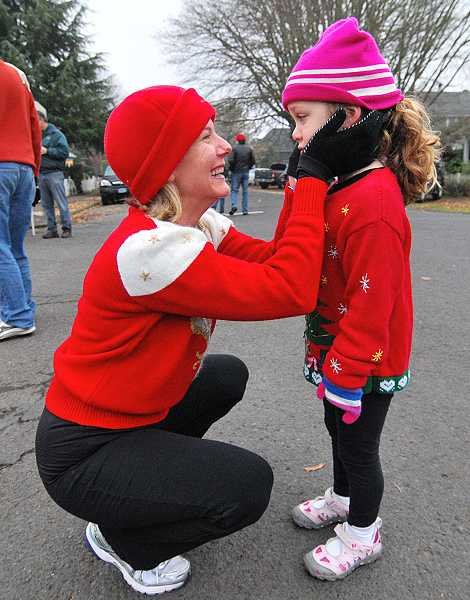 by: VERN UYETAKE - Sarah Neudeck and Ava take a breather after the Ugly Holiday Sweater Race last year.