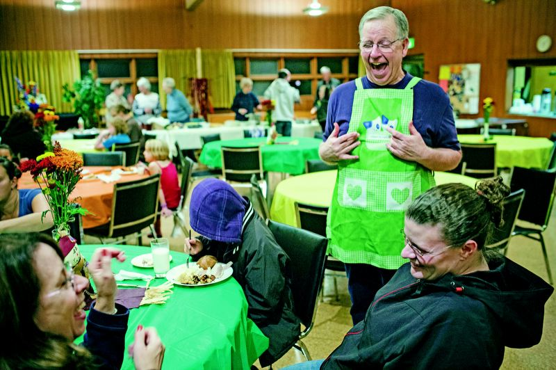 by: TRIBUNE PHOTO: CHRISTOPHER ONSTOTT - Volunteer Don McClure of Parkrose Community United Church of Christ serves dinner and a friendly conversation to families at the church's homeless shelter.