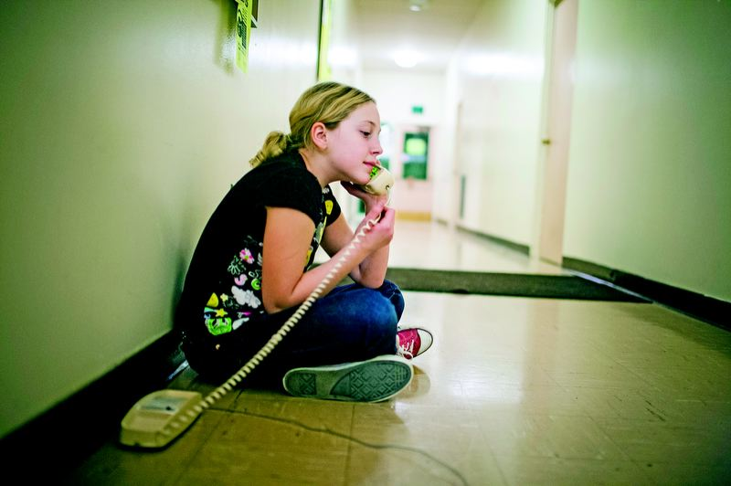 by: TRIBUNE PHOTO: CHRISTOPHER ONSTOTT - April, 10, talks with her grandmother on the free telephone in the church hallway before going to bed. Last week, April and her father were sleeping overnight in a park.