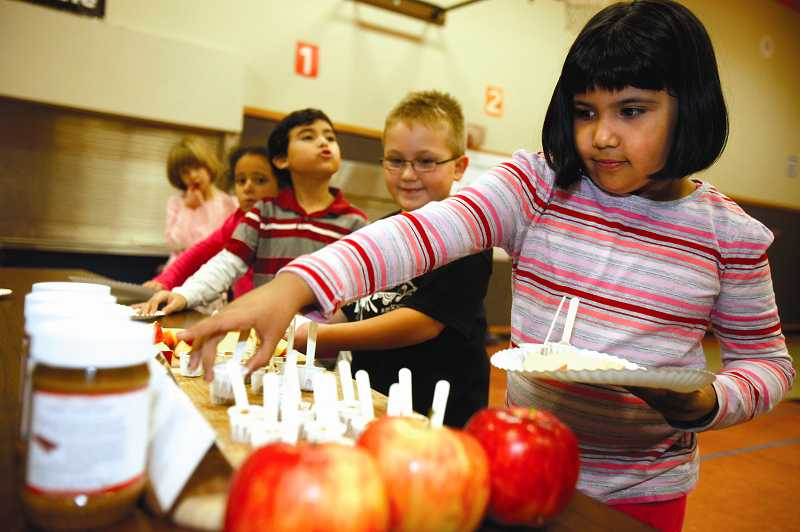 by: TIMES PHOTO: JONATHAN HOUSE - Kiara Salas grabs a helping of peanut butter to go along with her sliced apples during Melissa Gittelman's Healthy Snack Club at Durham Elementary.
