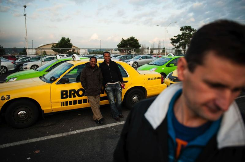 by: TRIBUNE PHOTO: CHRISTOPHER ONSTOTT - Taxi drivers wait as long as two hours at Portland International Airport for a fare, meaning low wages for drivers. Portland's cab drivers make on average $6.22 an hour, according to a city report. Many say a new union cab company could boost wages and provide better working conditions.