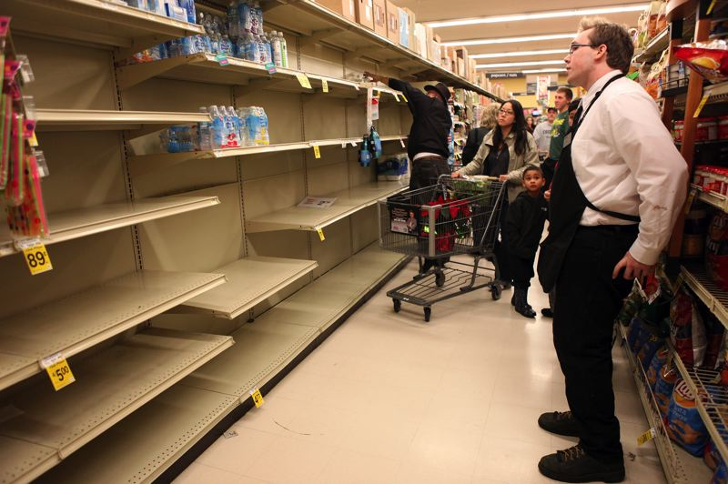 by: TIMES PHOTO: JAIME VALDEZ - Zack Cotner who works at the Safeway grocery store in Tigard, looks at the empty shelf which once stored bottled water. About 58,000 people were without water last week after the city issued a boil water notice.
