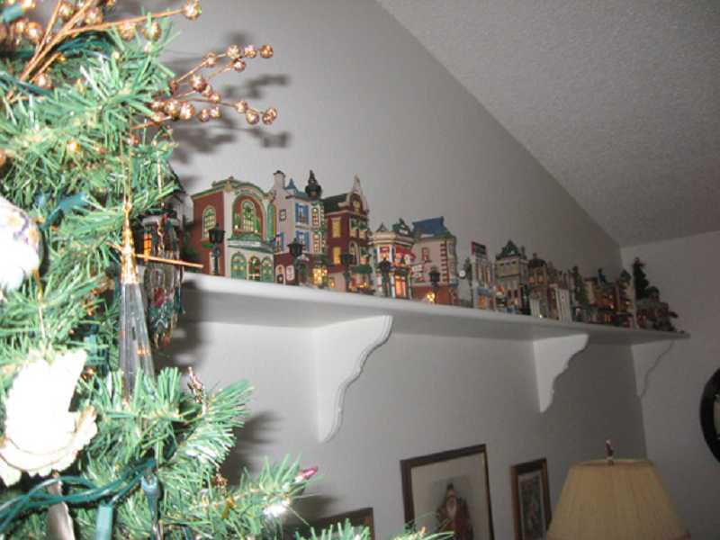 by: BARBARA SHERMAN - CHRISTMAS IN THE CITY -- Dee Schiavone leaves her Department 56 Christmas in the City collection set up all year long on high shelves in the living room.