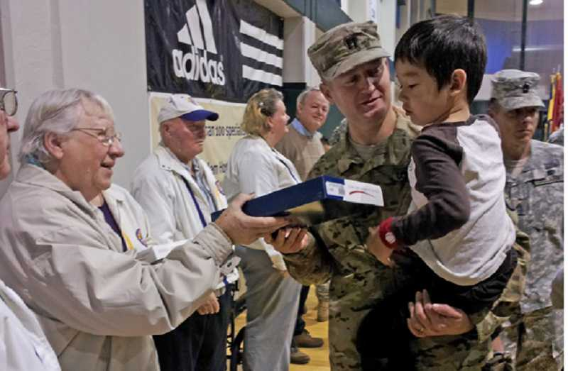by: COURTESY OF JENNIFER FAIR - GRATITUDE - Lions Club member Mary Thibert hands a flag to a returning soldier and his son following the National Guards Oct. 27 demobilization ceremony in Salem.