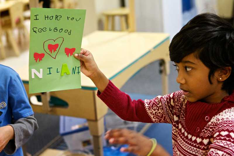 by: JAIME VALDEZ - Nilani Maheswaran, 5, a kindergartner at the Children at Bright Horizons children's center, shows her finished card to her teacher. The children made cards and care packages for kids in the Northeast affected by the Sandy super storm.