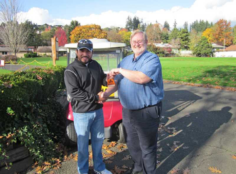 by: BARBARA SHERMAN - GOOD TIMES AHEAD - King City Pro Shop manager Harold Washam (right) hands Victor Alvarizares his annual pass, which the avid golfer has already started using.