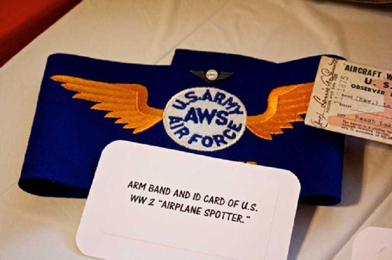 by: JEAN LEIDINGER - SHARING MEMORABILIA AND STORIES - At the Eldorado Villas second annual Veterans Day breakfast, one of the items on display was an arm band and ID card from a wartime airplane spotter.