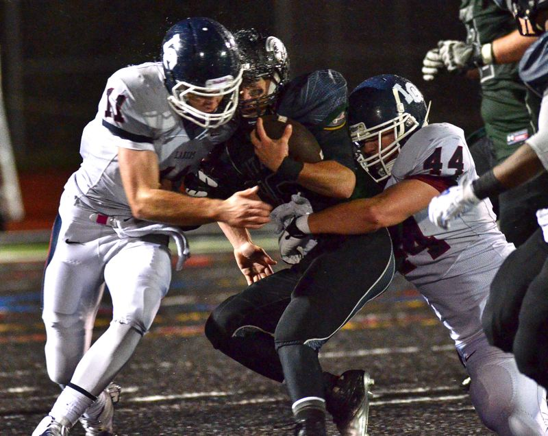 by: VERN UYETAKE - Lake Oswego's Jack Anderson, left, and Mitch Lomax combine to make a big hit during the Lakers' quarterfinal victory over West Salem. The Lake Oswego defense shut out the Titans in the second half to nail down a 28-7 victory.