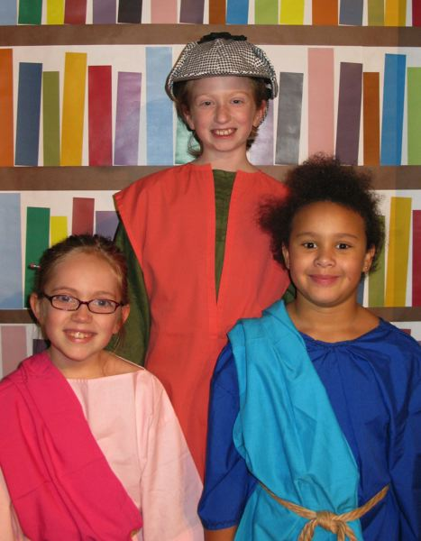 by: SHANNON BANKY - Pictured left to right are: Keilah Sander, the librarian, Bella Sigler, Sherlock Watson and Sasha Drummond, story teller.
