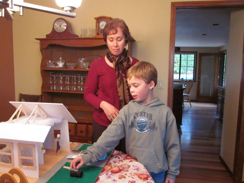 by: PHOTO BY ELLEN SPITALERI - Homeowner Marci Hartson listens to son, Daniel, as he points out the model of an energy-efficient home he constructed for a school project.
