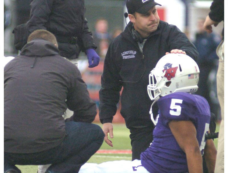 by: THE OUTLOOK: DAVID BALL - Linfield coach Joseph Smith comes onto the field to check on linebacker Dominique Forrest, who went down with a knee injury in the first quarter of Saturday's quarterfinal game.