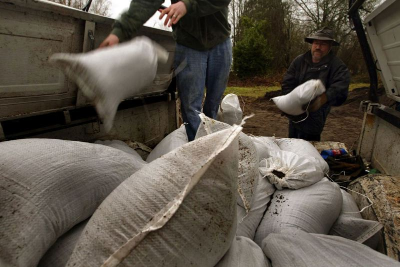 by: TRIBUNE FILE PHOTO - Flooding along Johnson Creek each year forces residents in the Foster Road area to stock up on sandbags. Portland officials are warning that a big storm blowing into the region Monday and Tuesday could create more flooding in area rivers and creeks.
