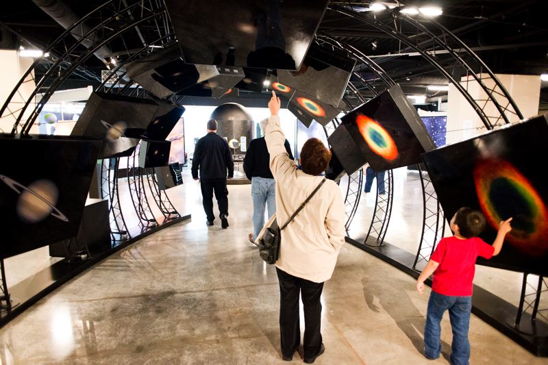 by: TRIBUNE PHOTO: CHASE ALLGOOD - Museumgoers take in the NASA exhibition during opening day at the new location of the Washington County Museum.