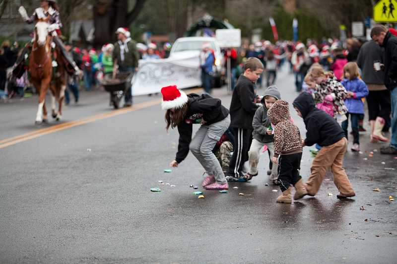 by: DARCI VANDENHOEK/KAZURIIMAGES.COM - Children scramble for the candy thrown from floats during the annual Winter Festival parade held Saturday in Sherwood.