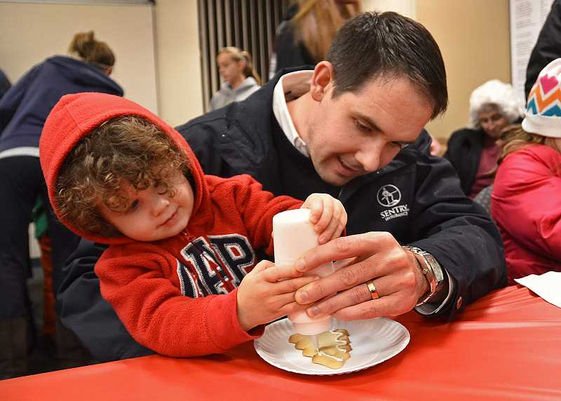 by: VERN UYETAKE - Kane Bailey and his son, 2-year-old Aiden, decorate a cookie inside city hall as part of the citys tree-lighting events.