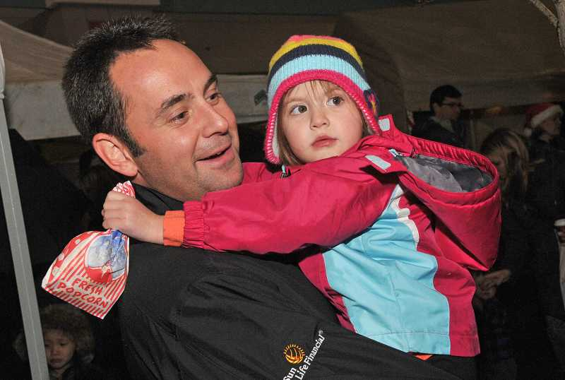 by: VERN UYETAKE - Jeff Amato and his daughter, Izzy, enjoy the tree-lighting festivities.