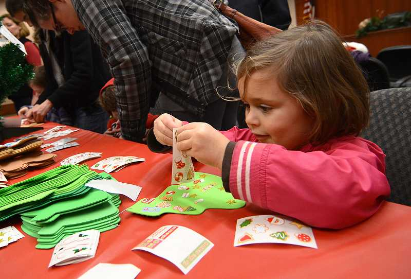 by: VERN UYETAKE - Lucy Troxel, 3, decorates a Christmas ornament.