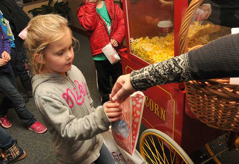 by: VERN UYETAKE - Leela Murphy gets a bag of popcorn at the West Linn tree lighting.