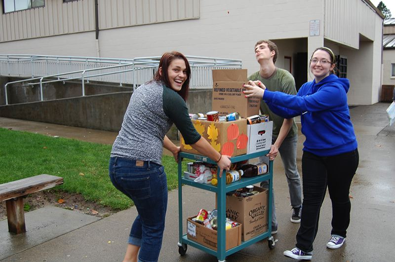 by: COURTESY PHOTO - Gaston High School students Kasey Cookston, Amber Meeks and Chris Waters with some of the nearly 1,000 cans collected for the Oregon Food Bank last month in a class competition.