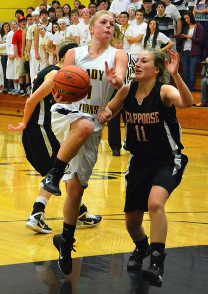 by: JOHN BREWINGTON - St. Helens' Nicole Harcourt goes up for a shot as Scappoose's Sarah Tinning defends. Harcourt would later scoring the game-winner as time waned. St. Helens won 27-26.