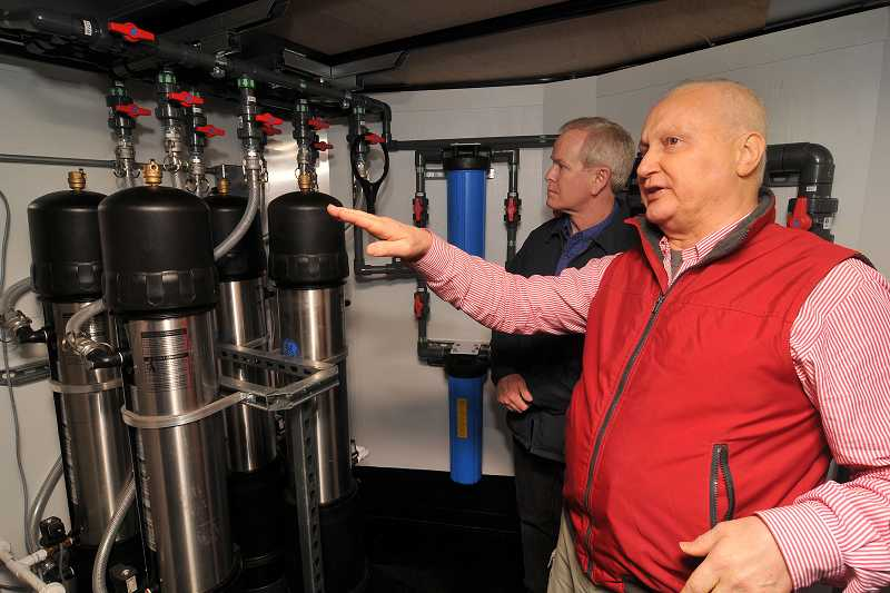by: VERN UYETAKE - Roddy Tempest of Tempest Environmental shows components of the city's new mobile water treatment system with Kevin Batridge, assistant water plant manager for Lake Oswego, examining equipment in the background.