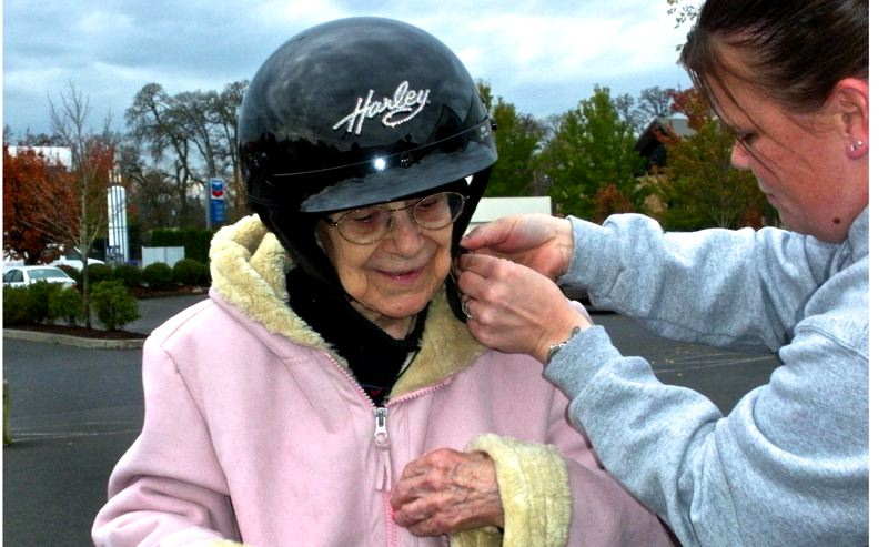 by: POST PHOTO: JIM HART - With a little help from Peah Salazar, right, of Latus Motors motorcycle clothing department, Dorothy Fairbanks, 103, dons a helmet before she gets her birthday wish, a ride on a motorcycle.