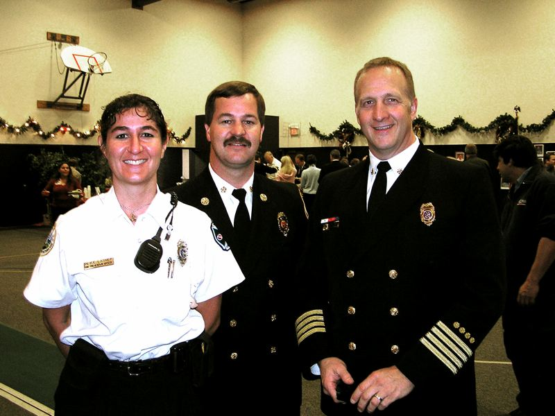 by: CONTRIBUTED PHOTO - Alice Busch, from left, standing with Chief Gary McQueen and Deputy Chief Rob Dahl, is leaving the Sandy Fire District after 14 years of service. CONTRIBUTED PHOTO