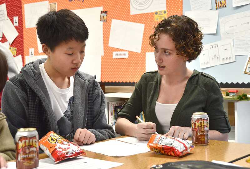 by: REVIEW PHOTO: VERN UYETAKE -  Seventh-grader Graham Kang works through a math problem with Mikaela Van Eaton's help.