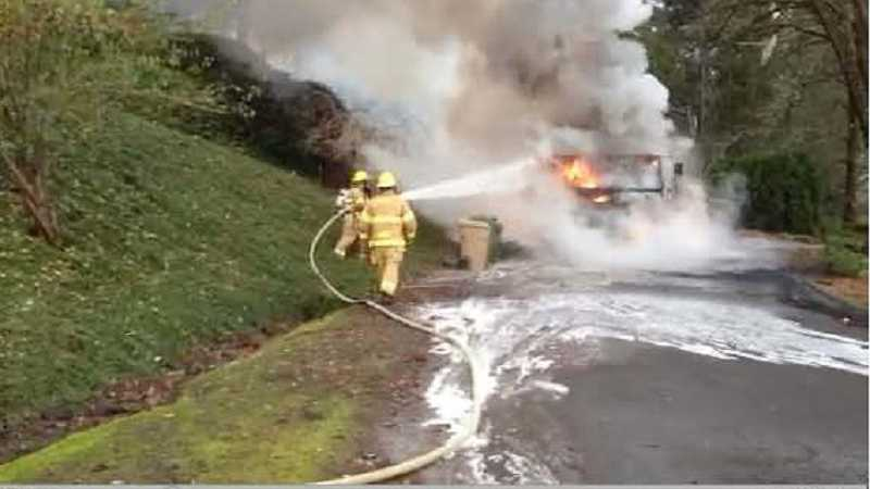 by: LAKE OSWEGO FIRE DEPARTMENT - Lake Oswego firefighters battle flames coming from an Allied Waste garbage truck Thursday morning.