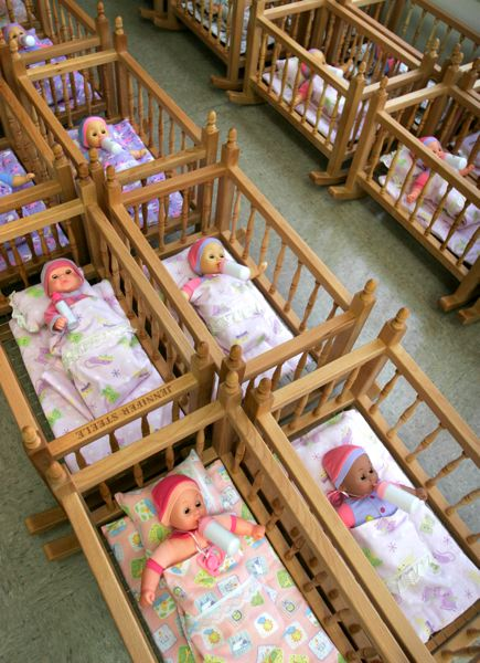 by: OUTLOOK PHOTO: JIM CLARK - Finished doll cribs, complete with three-piece bedding sets sewn by volunteer Boeing employees, plus dolls, sit ready to be delivered.