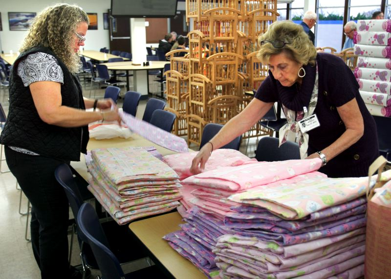 by: OUTLOOK PHOTO: JIM CLARK - Jennifer Steele, left, and Kaye Morrison fold blanket sets for cribs that Steele and four other volunteers sewed. Each of the 65 sets consists of a blanket, mattress and pillow. Steele has volunteered with Holiday Community Outreach Program for 25 years.