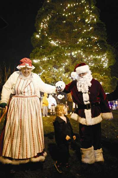 by: JAIME VALDEZ - Kenzie Hunt, 3, walks with Santa and Mrs. Clause at the Tigard Holiday Tree Lighting at Liberty Park in downtown Tigard