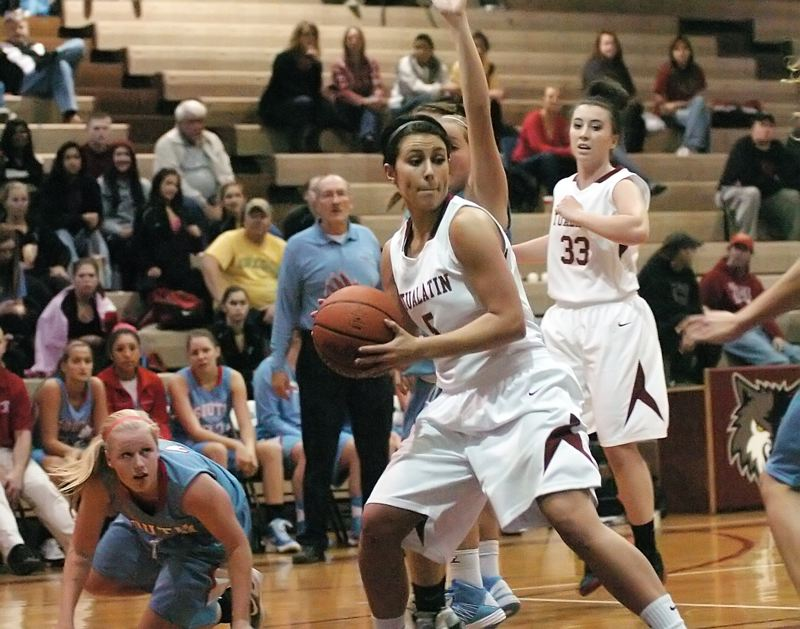 by: DAN BROOD - STAYING STRONG -- Tualatin senior guard Baylee Lyle keeps a firm grip on the ball during the Timberwolves' season-opener with South Salem.
