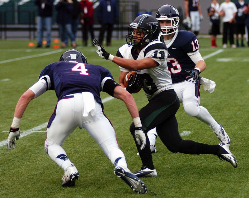 by: DAN BROOD - FINDING A SEAM -- Tigard High School junior receiver Darren Rodrigues (center) looks to cut between Lake Oswego's Jordan Horak (left) and Chad Walker after catching a pass in Saturday's semifinal game.