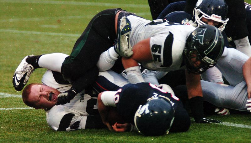 by: DAN BROOD - SENIOR SACK -- Tigard High School seniors Blake Chamberlain (without helmet) and Cain Adams combine to sack Lake Oswego quarterback Justen Ruppe in Saturday's state semifinal games.